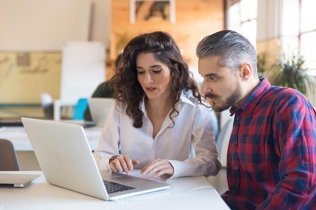 Poważni współpracownicy dyskutują o projekcie i wspólnie używają laptopa