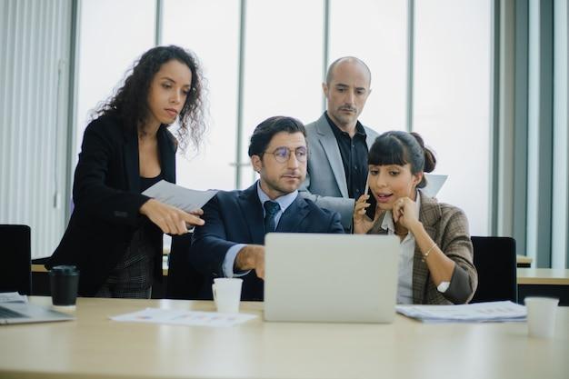 Poważni, zróżnicowani ludzie z międzynarodowego zespołu biznesowego omawiają przegląd wyników finansowych za pomocą laptopa.