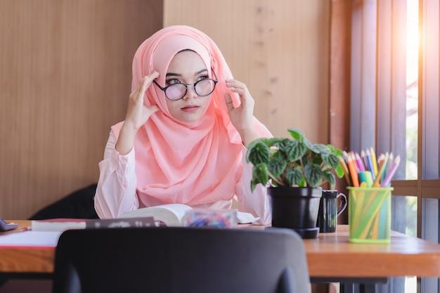 Poważnie azjatycka muzułmańska kobieta ma bóle głowy w biurze.