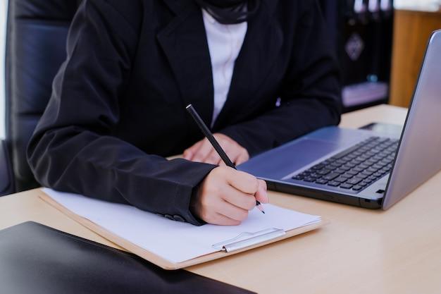 Poważnie bizneswoman pisze analizę dokumentu w biurze