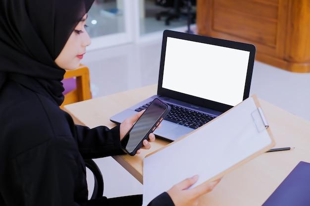 Poważnie młoda kobieta biznesu, posiadająca dokument finansowy w biurze i trzymając telefon komórkowy