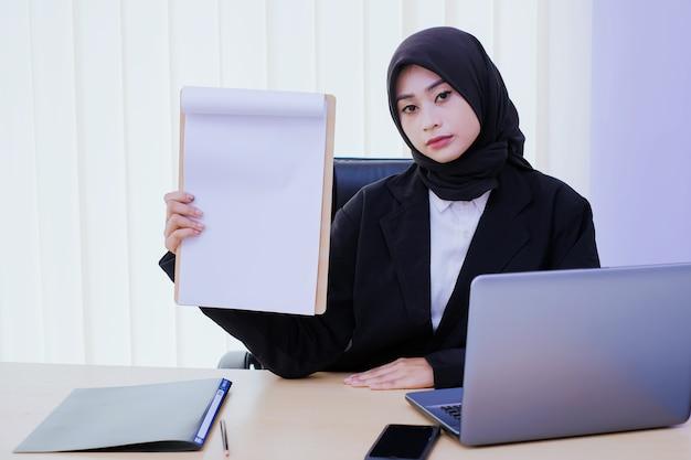 Poważnie młoda kobieta biznesu posiadająca dokument finansowy w biurze