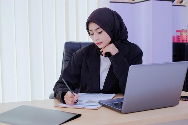 Poważnie młoda kobieta biznesu siedzi przy biurku, analizując dokument