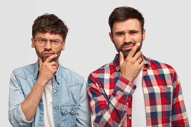 Poważnie sfrustrowani młodzi europejczycy trzymają podbródki i patrzą z ponurą miną, zastanawiają się nad czymś ważnym, noszą zwykłe ubrania, odizolowani na białej ścianie. przyjaciele mają zamyślony wygląd