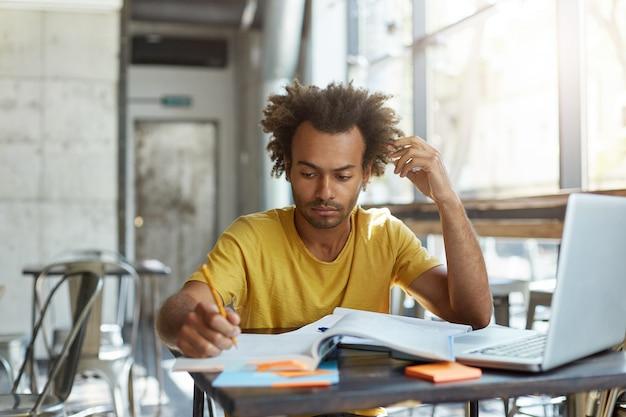 Poważnie skupiony młody student z afryki w żółtej koszulce, zajęty wykonywaniem prac domowych, spisywaniem w zeszycie ćwiczeń, siedzeniem w pustej przestrzeni coworkingowej wczesnym rankiem, przy użyciu laptopa