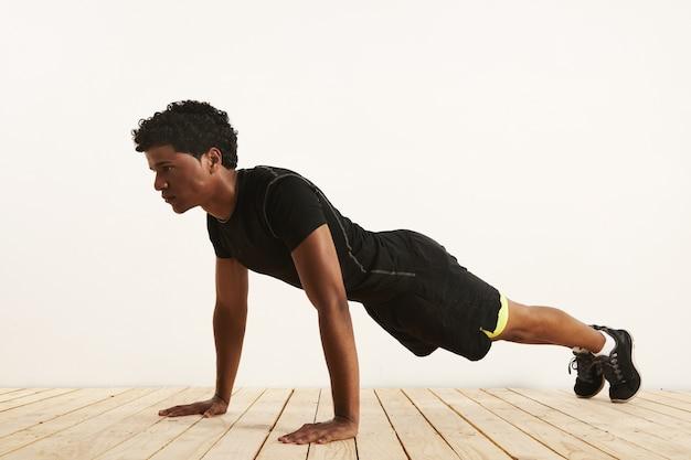 Poważnie sprawny czarny afroamerykanin wykonujący pompkę z lekkiej drewnianej podłogi na białej ścianie