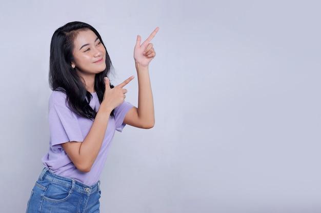 Poważnie szczęśliwa azjatycka kobieta z prawym palcem wskazującym i odizolowana na jasnym białym tle transparentu z miejscem na kopię