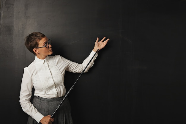 Poważnie wyglądająca młoda biała nauczycielka w białej bluzce z guzikami i tweedową spódnicą stoi na czarnej tablicy trzymając wskaźnik