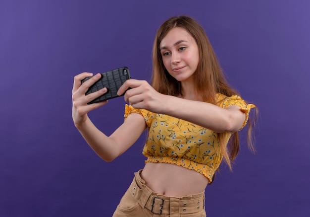 Poważnie wyglądająca młoda dziewczyna przy selfie na na białym tle fioletowej przestrzeni
