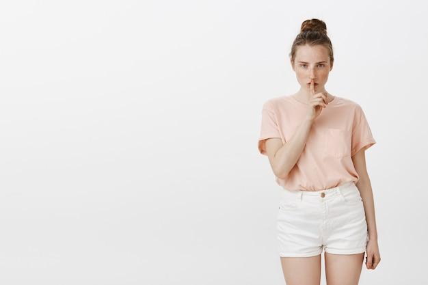 Poważnie wyglądająca nastolatka pozuje na białej ścianie