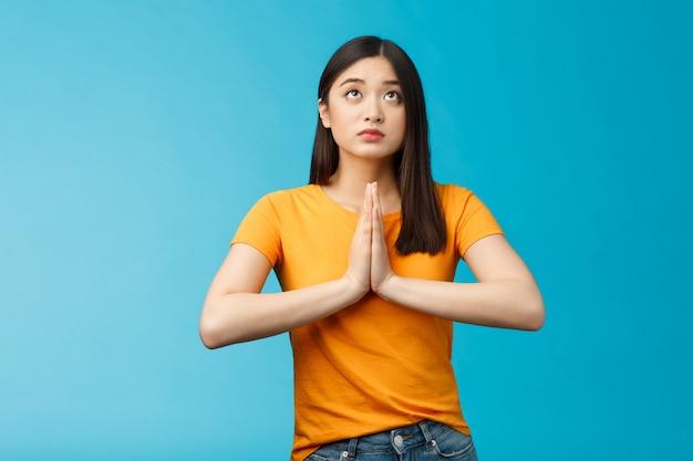 Poważnie wyglądająca, pełna nadziei, urocza azjatycka kobieta błagająca bóg wysłuchaj modlitw, błagając, sprawiając, że życzysz sobie, by spojrzeć na niebo rozmawiające lors, uwierz mieć wiarę, stać na niebieskim tle błagając o szczęście