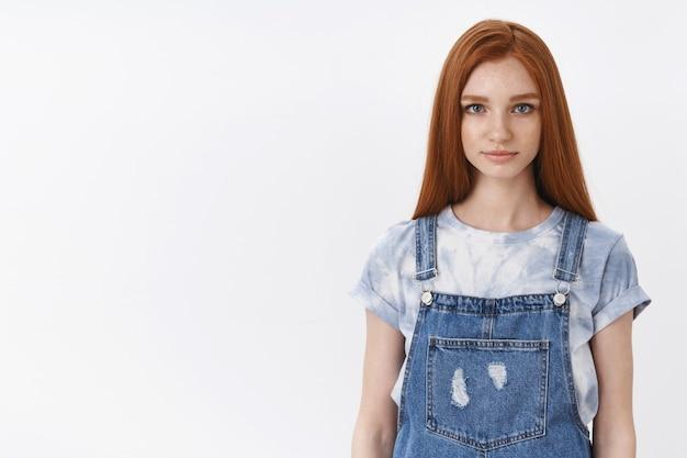 Poważnie wyglądająca rudowłosa nastolatka o niebieskich oczach wygląda na szczerą, pełną nadziei, prowadzi ważną rozmowę, coś ciekawego ci powie, miłą rozmowę, stoi białe dżinsowe kombinezony ścienne