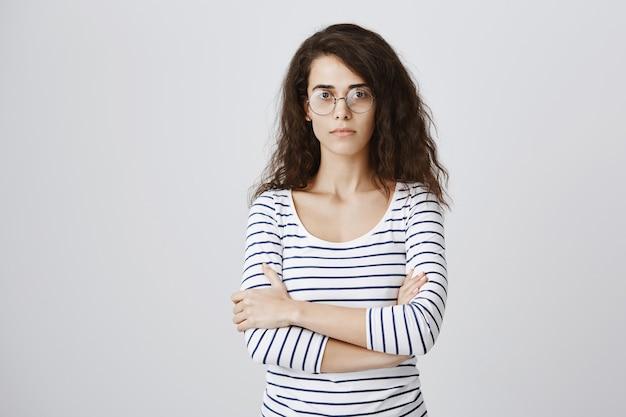 Poważnie wyglądająca studentka w nerdowskich okularach, pewna siebie ze skrzyżowanymi ramionami