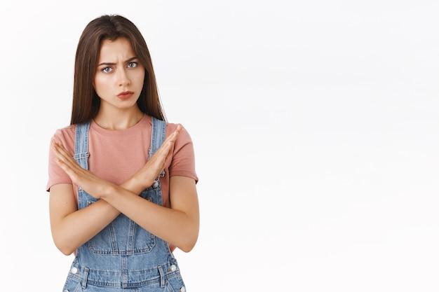 Poważnie wyglądająca wściekła brunetka w dżinsowych ogrodniczkach, t-shircie, która sprawia, że ktoś się zatrzymuje, zapobiega złej decyzji, potrząsa głową w negatywnej odpowiedzi, nie zgadza się, zakazuje lub odrzuca ofertę