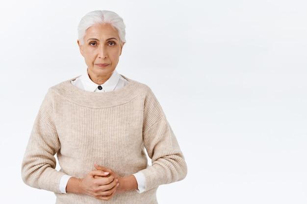 Poważnie wyglądający elegancki starszy nauczyciel, dyrektor na służbie, noś strój biurowy, sweter na bluzie, trzymaj ręce razem na klatce piersiowej, patrz na aparat surowo i zdeterminowany, asertywna biała ściana