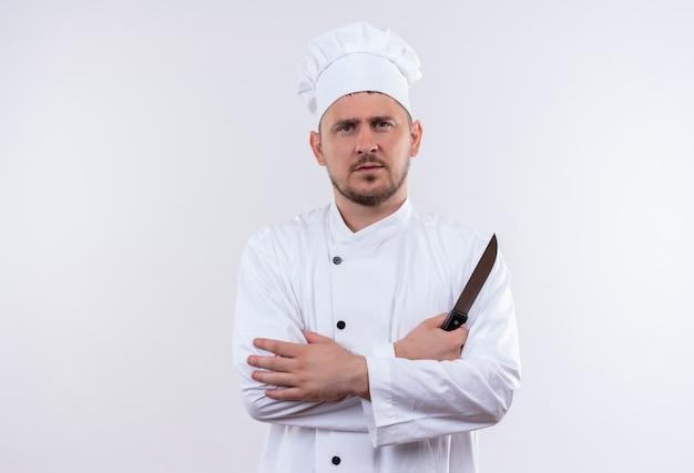 Poważnie wyglądający młody przystojny kucharz w mundurze szefa kuchni stojący z zamkniętą posturą i trzymając nóż na białym tle