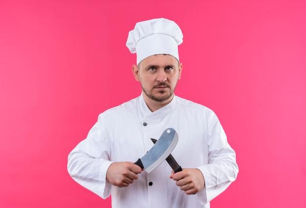 Poważnie wyglądający młody przystojny kucharz w mundurze szefa kuchni trzymając tasak i nóż na białym tle na różowej przestrzeni