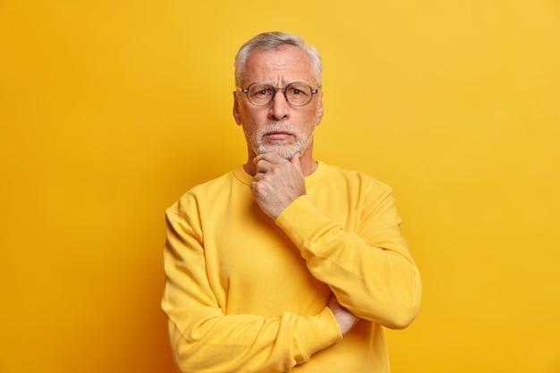 Poważnie wyglądający zdziwiony, brodaty, siwowłosy przystojny mężczyzna trzyma podbródek i patrzy bezpośrednio z przodu ubrany w swobodny sweter odizolowany na żółtej ścianie