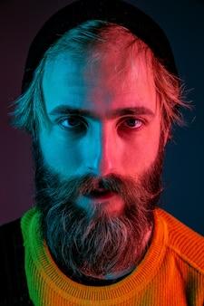 Poważnie, z bliska. portret mężczyzny rasy kaukaskiej na przestrzeni gradientu w świetle neonu
