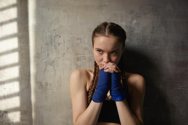 Poważnie zdeterminowana nastolatka z dwoma warkoczami pozująca przy pustej teksturowanej ścianie, ubrana w niebieskie bandaże, zaciskająca ręce na twarzy, gotowa do zajęć bokserskich