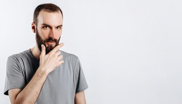 Poważnie zdziwiony przystojny model z brodą, trzymający rękę na brodzie, jakby o czymś myślał, mrużąc oczy z podejrzliwym spojrzeniem i stojąc nad szarym tłem. człowiek decyduje, co kupić