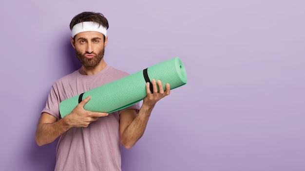 Poważnie zmotywowany mężczyzna z grubym włosiem, trzyma zwinięty kareamt, robi grymas, gotowy do treningu jogi, nosi codzienne ubrania