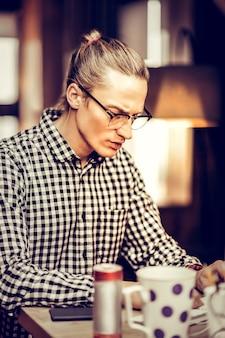 Poważność w pracy. pewny siebie freelancer w okularach podczas pracy przy komputerze