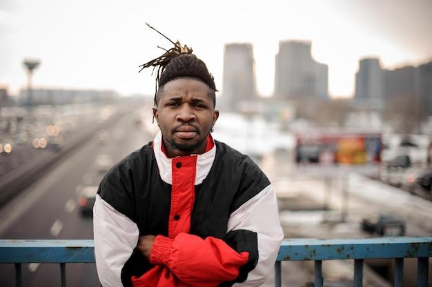 Poważny afro-amerykański mężczyzna stojący na drodze miasta, krzyżując ręce