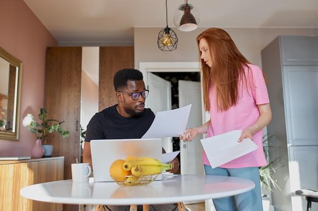 Poważny afrykański mężczyzna czyta dokumenty, a kaukaska kobieta omawia niezapłacone rachunki wewnętrzne