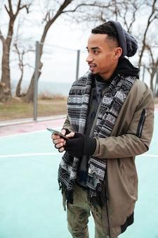 Poważny afrykański mężczyzna trzyma telefon komórkowego outdoors i używa