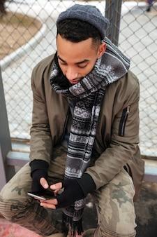 Poważny afrykański mężczyzna używa telefon komórkowego outdoors