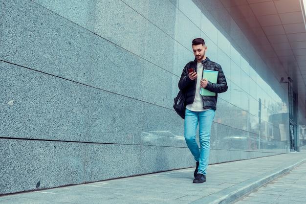 Poważny arabski student używający smartfona w centrum miasta