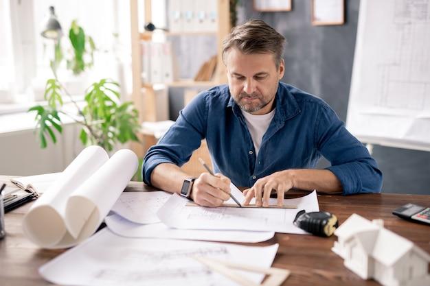 Poważny architekt w codziennej odzieży siedzi przy stole podczas pracy nad nowym projektem lub rysuje linię, aby zakończyć szkic