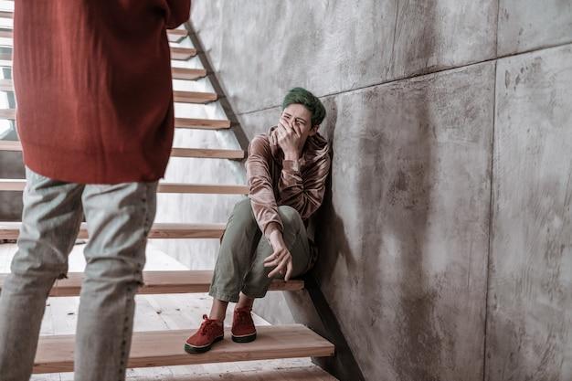 Poważny argument. dziewczyna z krótko ściętymi włosami płacze po poważnej kłótni z chłopakiem