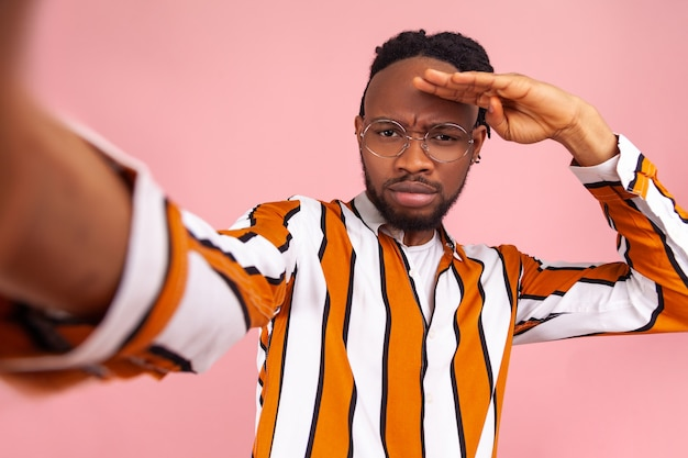 Poważny, asertywny afrykański bloger z dredami, w koszuli w paski, spoglądający daleko z ręką nad głową, szukający nowych subskrybentów, pozujący do selfie. kryty studio strzał na białym tle na różowym tle