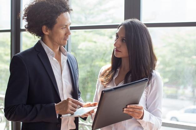 Poważny asystent daje dokumentom biznesmen