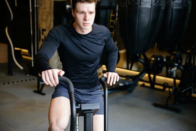 Poważny atletyczny mężczyzna używa przędzalnianego bicykl