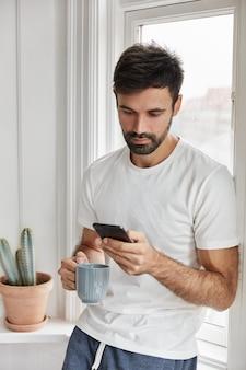 Poważny atrakcyjny facet pozuje w domu w swoim domu