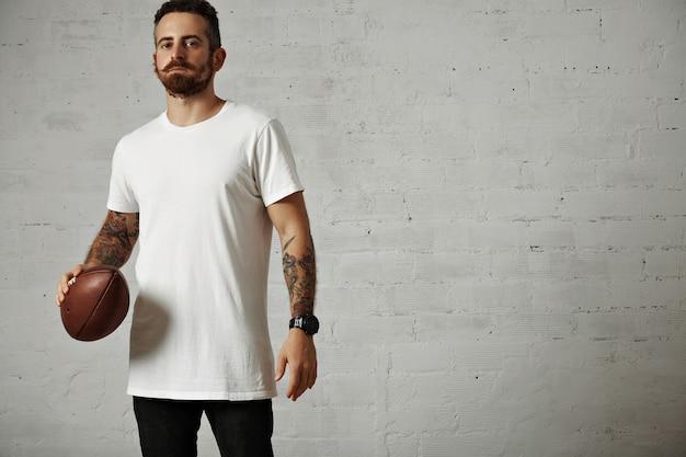 Poważny atrakcyjny młody człowiek w pustej białej bawełnianej koszulce i czarnych dżinsach trzyma piłkę rocznika rugby na białym tle
