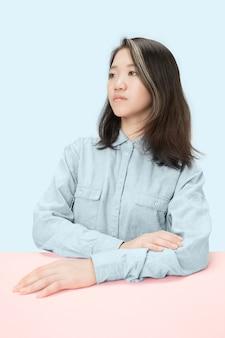 Poważny biznes kobieta siedzi przy stole, patrząc na lewo na białym tle na modnym niebieskim studio.