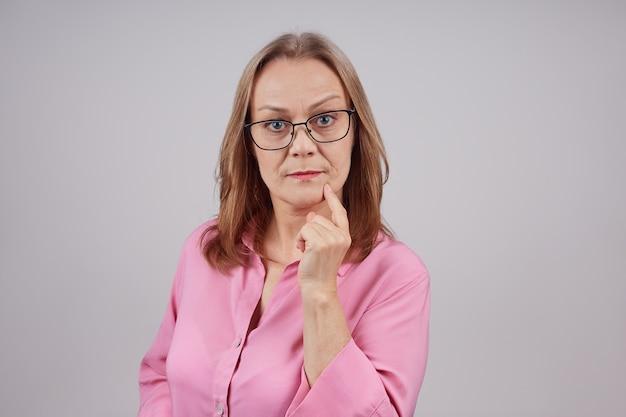 Poważny biznes kobieta w okularach pozowanie, patrząc w kamerę, dłoń na brodzie. zdjęcie na szarym tle z miejsca na kopię.