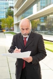 Poważny biznesmen bierze notatki na ulicie