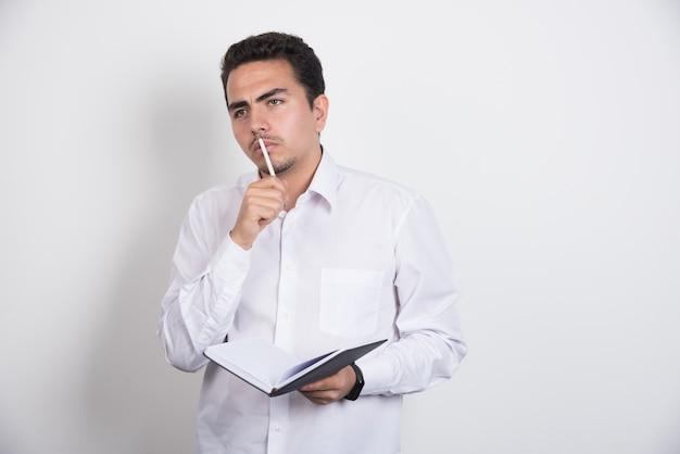 Poważny biznesmen ciężko myśli notebook na białym tle.