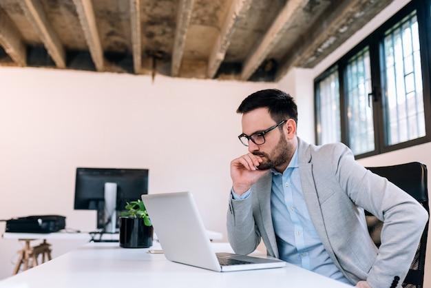 Poważny biznesmen patrzeje laptopu ekran.