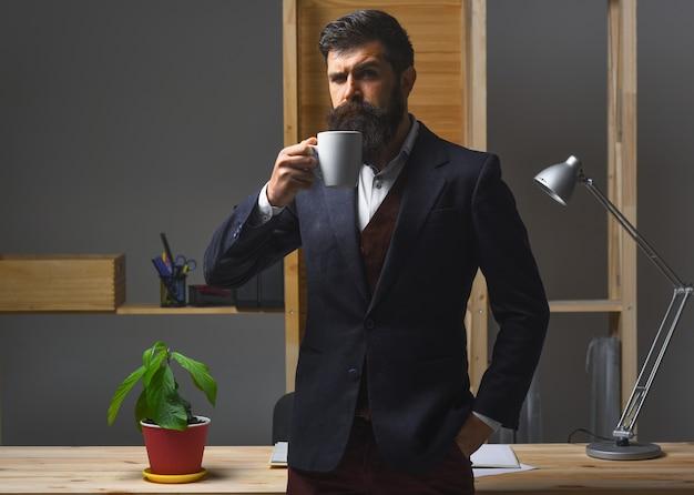 Poważny biznesmen pijący kawę w biurze gorące napoje kawowe portret znacznej brodaty