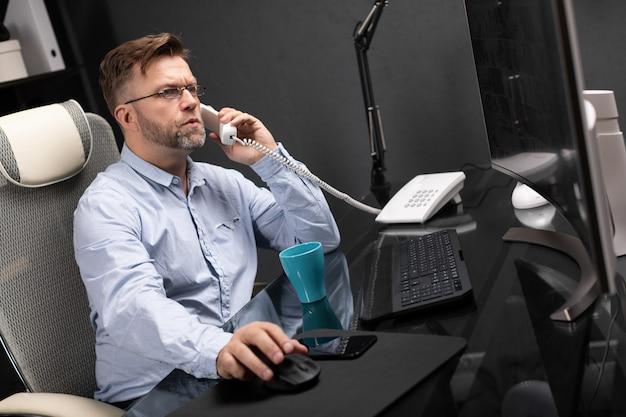Poważny biznesmen pracuje w biurze przy komputerem biurko i opowiada na telefonie stacjonarnym