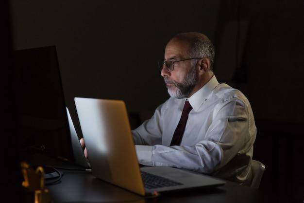 Poważny biznesmen pracuje z laptopem póżno przy nocą