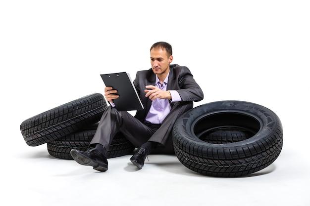 Poważny biznesmen siedzi na stosie opon samochodowych. warsztat. serwis samochodowy. odsprzedaż części zamiennych. na białym tle