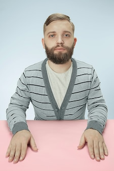 Poważny biznesmen siedzi przy stole na niebieskim studio.