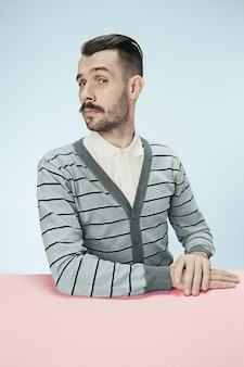 Poważny biznesmen siedzi przy stole. portret w stylu minimalizmu w profilu